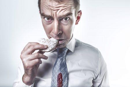 homme entrain de manger un donut tache sur cravate